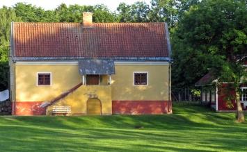Ett märkligt hus strax utanför herrgårdens staket ... små fönster, en konstig veranda ... och dörren där under...