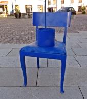 på torget står en blåmålad stol med en blå blomkruka ...