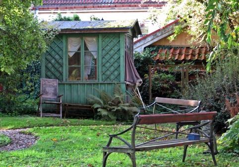 Ett litet grönt hus och en bänk i samma trädgård