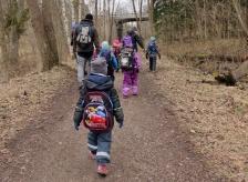 Barnen bär ryggsäckar på väg till skogen.