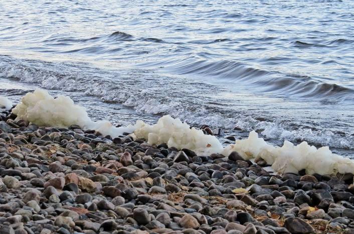 vinden piskade upp vågorna som rulllade in mot stranden och bildade vitt skum ...