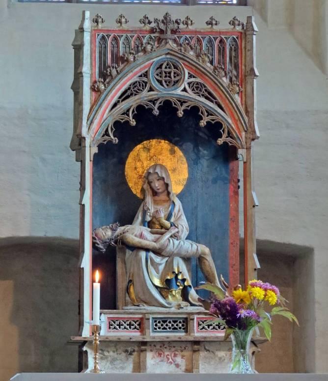 Altarprydnaden är en Pietà, (av italienskans pietà - förbarmande), motiv inom konsten föreställande jungfru Maria med den döde Kristus i famnen.
